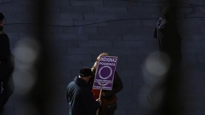 "A man holds a placard in support of Spain's party ""Podemos"" (We Can) as he gathers, before the start of a rally called by Podemos, at Madrid's landmark Puerta del Sol"