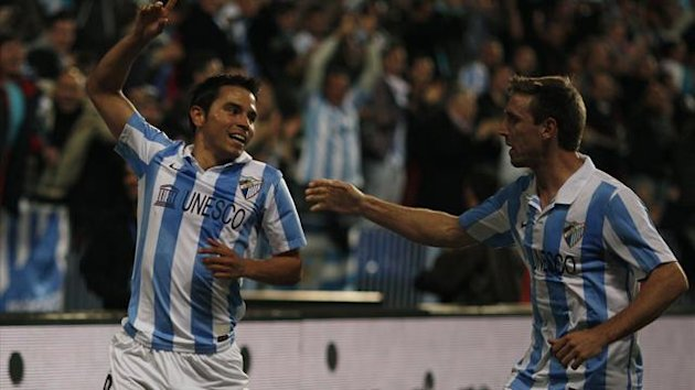Malaga&#39;s Javier Saviola (L) celebrates with his team mate Ignacio Monreal after scoring a goal against Granada during their Spanish First Division soccer match at La Rosaleda (Reuters)
