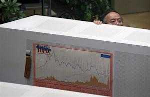 An employee of the Tokyo Stock Exchange (TSE) looks at a monitor at the bourse before the market opened for the new year in Tokyo January 6, 2014. REUTERS/Toru Hanai