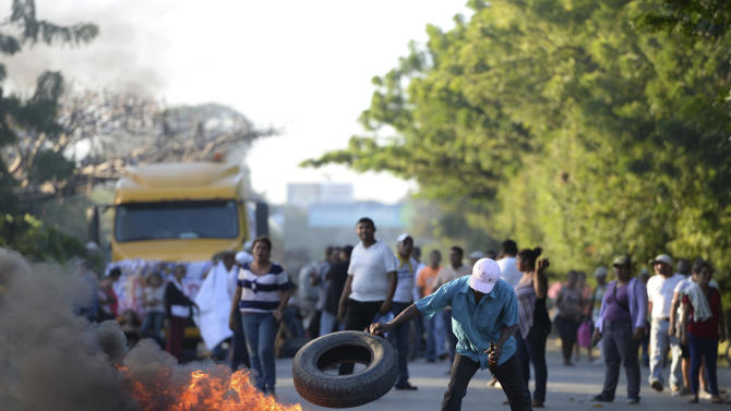 Residents burn tires at a blockade on the Pan-American highway  during the groundbreaking day of the $50 billion transoceanic waterway construction project predicted to rival the Panama Canal, in Managua, Nicaragua, Monday, Dec. 22. 2014.  The groundbreaking marked the start of some ancillary projects in Brito, a city about 5 kilometers (3 miles) from Nicaragua's Pacific coast where the first port will be built. Officials say the canal will be fully operational by 2019.(AP Photo/La Prensa, Oscar Navarrete)