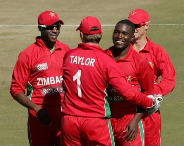 Zimbabwe's bowler Elton Chigumbura (R) celebrates a wicket with Vusimuzi Sibanda (L) and teammates  during the first match of the five match ODI cricket series between India and hosts Zimbabwe at