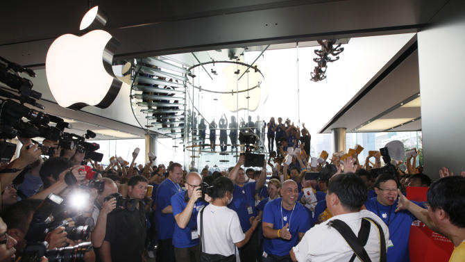 FILE - In this Saturday, Sept. 24, 2011 file photo, customers cheer with staff members of Apple Inc. at the new store in Hong Kong's upscale International Financial Center Mall. Apple rolled out its iTunes online store to Hong Kong, Taiwan and 10 other Asian countries Wednesday, June 27, 2012, in a broad push to sell music and video to more users in the company's fastest growing region. (AP Photo/Kin Cheung, File)