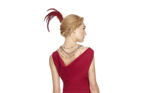 """This image released by Banana Republic shows Crimson Cowl-Back Dress, styled with crystal and topaz layered bead necklaces and a red feather from a limited-edition collection designed by Banana Republic. Led by Creative Director and EVP, Simon Kneen, and styled and curated by """"Anna Karenina"""" costume designer Jacqueline Durran, the collection is currently available in Banana Republic stores. (AP Photo/Banana Republic)"""