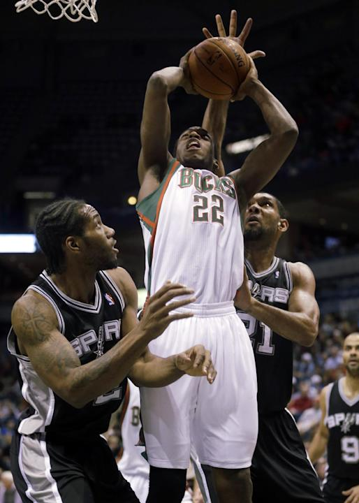 Milwaukee Bucks' Khris Middleton(22) has his shot blocked as he goes up against San Antonio Spurs' Tim Duncan (21) and Kawhi Leonard during the first half of an NBA basketball game Wednesday,