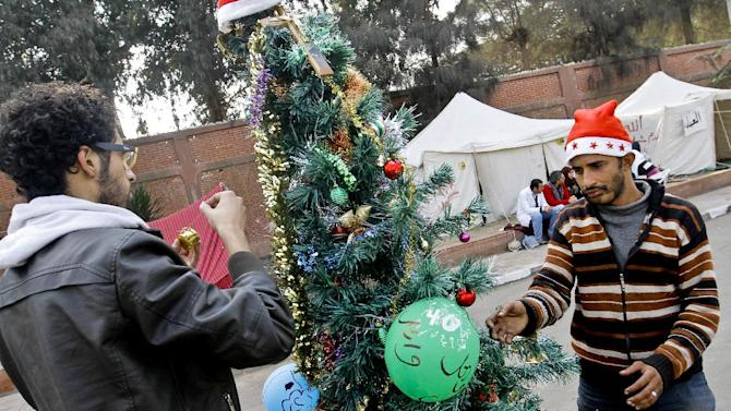 Egyptian protesters decorate a Christmas tree near the presidential palace in Cairo, Egypt, Monday, Dec. 31, 2012. Protesters will celebrate New Year's eve in front of the presidential palace. (AP Photo/Amr Nabil)
