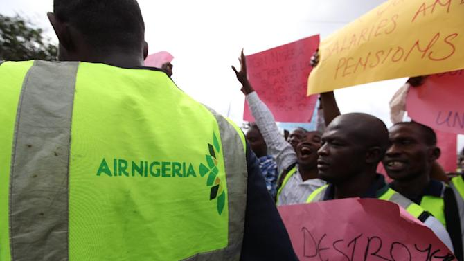 """Former Air Nigeria staff protest after they were fired in Lagos, Nigeria, Friday, Sept. 7, 2012. More than 60 workers from Air Nigeria protested Friday at Lagos' Murtala Muhammed International Airport's domestic terminal, demanding four-months-worth of unpaid salaries from the company. The airline's owner, business tycoon Jimoh Ibrahim, fired nearly all of the company's 800 employees for """"disloyalty"""" earlier this month. (AP Photo/Jon Gambrell)"""