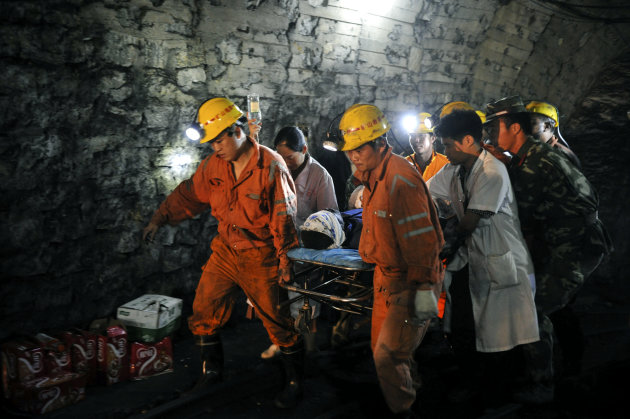 Liu Yunqing, the first miner rescued, is carried out on a stretcher from the flooded pit of Qielichong colliery in Sandu Township of Leiyang City, central China's Hunan Province, on Sunday, July 8, 2012. Chinese rescuers pulled to safety the first three of about a dozen miners trapped underground for more than three days in the flooded coal mine pit. (AP Photo/Xinhua, Bai Yu) NO SALES