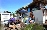 A Philippine mother-of-two talks on her mobile phone as she crouches on top of a tomb that has served as her family's temporary home in Calumpit since August 8. As floods which have swamped parts of the Philippines and affected more than two million people extend into their second week, the dead and the living are sharing premium space on dry ground