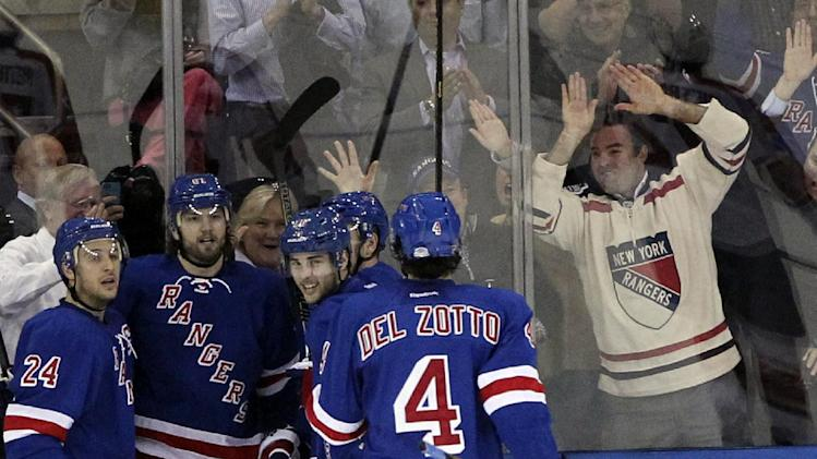 New York Rangers Derick Brassard, third from left, celebrates with teammates and fans after scoring a goal during the first period of an NHL hockey game against the Florida Panthers, Thursday, April 18, 2013 at Madison Square Garden in New York.  (AP Photo/Mary Altaffer)