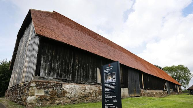 In this photo taken on Tuesday, May 19, 2015, Harmondsworh Great Barn, a medieval timber framed barn built in 1426-7 stands in Harmondsworth in London. Residents of the village close to Heathrow Airport are campaigning against the expansion of the airport which they claim will decimate their community. (AP Photo/Kirsty Wigglesworth)