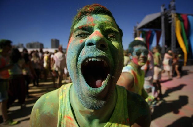 A reveller reacts as he is covered in coloured cornflour powder while participating in the Holi One festival in Cape Town