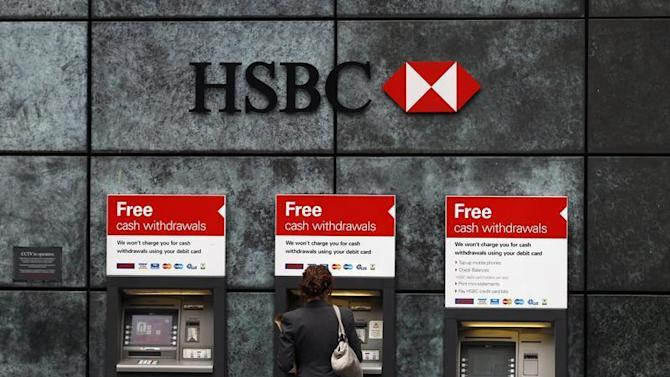 A woman uses a cash point machine at a HSBC bank in the City of London