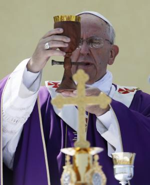 ADDS INFORMATION ABOUT THE CHALICE. Pope Francis celebrates a Mass with a chalice made from recycled wood from broken migrant boats, during his visit to the island of Lampedusa, southern Italy, Monday July 8, 2013. Pope Francis traveled Monday to the tiny Sicilian island of Lampedusa to pray for migrants lost at sea, going to the farthest reaches of Italy to throw a wreath of flowers into the sea and celebrate Mass as yet another boatload of Eritrean migrants came ashore. (AP Photo/Gregorio Borgia)