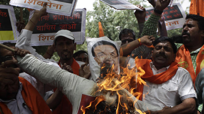 About two dozen members of Shiv Sena, a Hindu right-wing political party, burn an effigy of Chinese Premier Li Keqiang as they demonstrate near India's Parliament, in New Delhi, India, Sunday, May 19, 2013. Just weeks after a tense border standoff, China's new premier headed to India on Sunday for his first foreign trip as the neighboring giants look to speed up efforts to settle a decades-old boundary dispute and boost economic ties. (AP Photo/Tsering Topgyal)