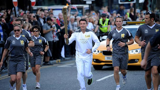 FILE This Monday June 25, 2012 file image made available by LOCOG shows torchbearer 140 Lord Sebastian Coe carrying the Olympic Flame on the Torch Relay leg through Sheffield, England. No one is more closely associated with the London Games than Coe, the former two-time Olympic gold medalist in the 1,500 meters. He led the city's winning bid for the Olympics and has spent seven years chairing the local organizing committee for the biggest peacetime project in British history.(AP Photo/Ben Birchall, LOCOG)