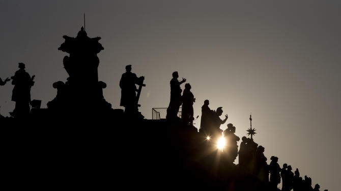 The sun sets behind the statues on top of the Bernini colonnade in St. Peter Square, at the Vatican, Monday, March 4, 2013. Cardinals from around the world have gathered inside the Vatican for their first round of meetings before the conclave to elect the next pope, amid scandals inside and out of the Vatican and the continued reverberations of Benedict XVI's decision to retire. (AP Photo/Andrew Medichini)