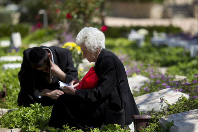 Rachel Falah the widow of Abraham Falah, who was killed in the 1967 Mideast War reads from a holy book as she sits with their son next to his grave at the Kiryat Shaul Military Cemetery in Tel Aviv, Israel, Sunday, April 14, 2013. Israel will mark the annual Memorial Day in remembrance of soldiers who died in the nation's conflicts, beginning at dusk Sunday until Monday evening. (AP Photo/Ariel Schalit)