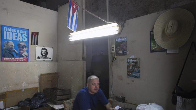 Pictures of Fidel Castro, Raul Castro and Che Guevara hang in a shop as attendant Reinaldo Perez talks to a client in downtown Havana