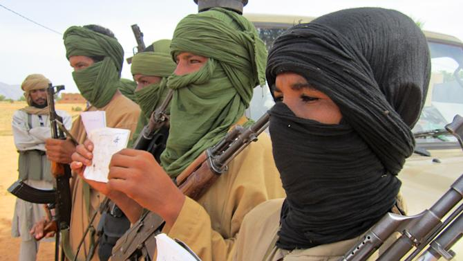 In this Thursday, Sept. 27, 2012 photo, young fighters, including 13-year-old Abdullahi, right, and 14-year-old Hamadi, second right, display their Quranic studies notes for a journalist as their Islamist commanders look on, in Douentza, Mali.  Islamists in northern Mali have recruited and paid for as many as 1,000 children from rural towns and villages devastated by poverty and hunger. The Associated Press spoke with four children and conducted several dozen interviews with residents and human rights officials. The interviews provide evidence that a new generation in what was long a moderate and stable Muslim nation is becoming radicalized, as the Islamists gather forces to fight a potential military intervention backed by the United Nations. (AP Photo/Baba Ahmed)