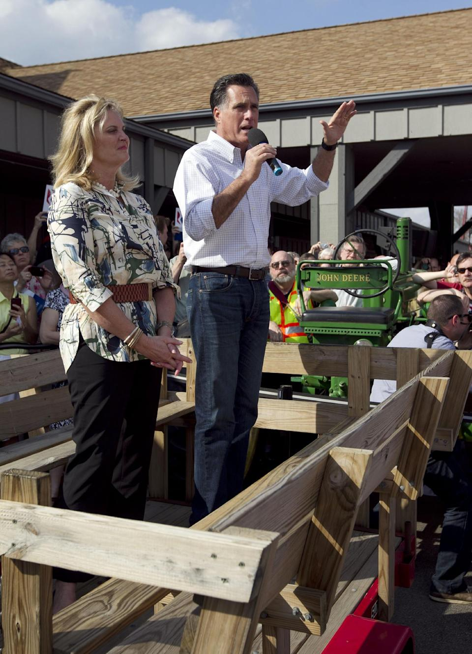 Republican presidential candidate, former Massachusetts Gov. Mitt Romney, right, addresses an audience from a wood wagon as his wife Ann, left, looks on during a campaign stop in Rockford, Ill., Sunday, March 18, 2012. (AP Photo/Steven Senne)