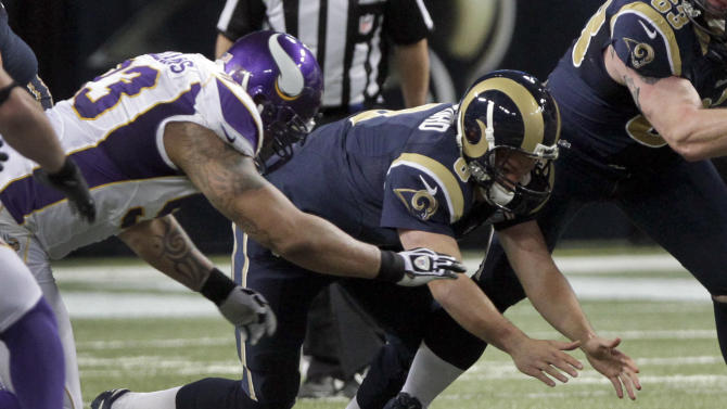 St. Louis Rams quarterback Sam Bradford, right, and Minnesota Vikings defensive tackle Kevin Williams reach for a ball fumbled by Bradford during the second quarter of an NFL football game Sunday, Dec. 16, 2012, in St. Louis. The Vikings' Chad Greenway recovered the fumble. (AP Photo/Seth Perlman)