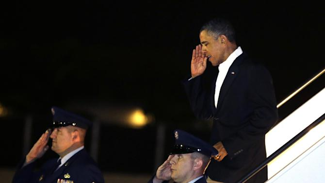 President Barack Obama salutes as he gets off Air Force One upon his arrival at Joint Base Pearl Harbor-Hickam in Honolulu, Hawaii, Wednesday, Jan. 2, 2013. The president is back in Hawaii for vacation after a tense, end-of-the-new-year standoff with Congress over the fiscal cliff. (AP Photo/Gerald Herbert)