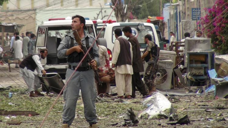 Security officials conduct investigation at the scene of suicide bomb attacks in Jalalabad, Afghanistan, Saturday, 3, 2013. Three suicide attackers killed at least nine civilians, most of them children, in a botched attack Saturday on the Indian consulate in an eastern Afghan city near the border with Pakistan, security officials said. (AP Photo/Babrak)