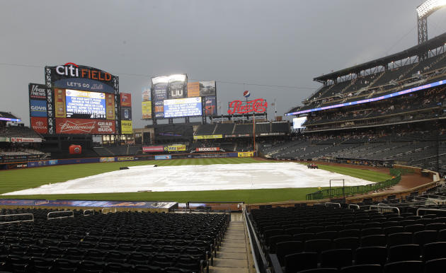 Citi Field is covered during a rain delay before an interleague baseball game between the New York Mets and the New York Yankees, Friday, June 22, 2012, in New York. (AP Photo/Frank Franklin II)
