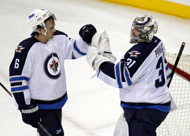 Jets defenseman Hainsey and goalie Pavelec congratulate each other on their win over the Rangers in their NHL hockey game in New York