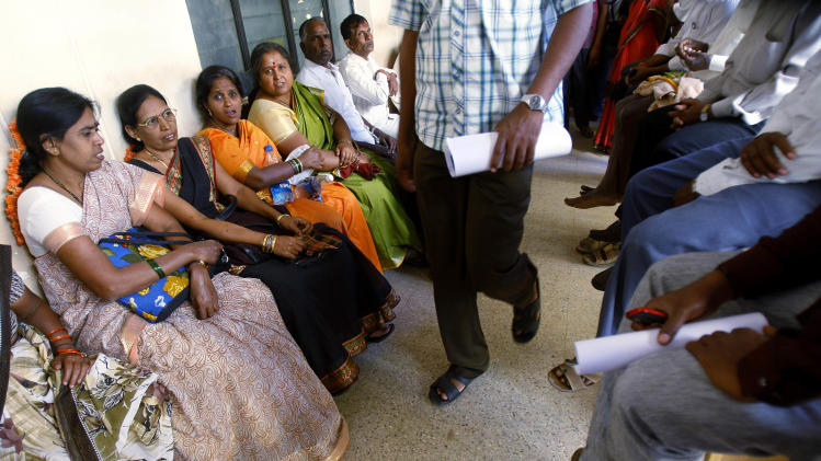 In this Dec. 10, 2012 photo, people wait to get their land registered at the government registrar's office in Hoskote 30 kilometers (19 miles) from Bangalore, India. For years, Karnataka's land records were a quagmire of disputed, forged documents maintained by thousands of tyrannical bureaucrats who demanded bribes to do their jobs. In 2002, there were hopes that this was about to change. (AP Photo/Aijaz Rahi)
