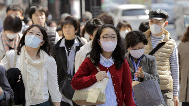 In this photo taken on March 16, 2013, people wearing masks walk down a street in Tokyo. Japan is becoming a sea of surgical masks. It's about pollen, about germs and even a little about China, its polluting rival across the sea. (AP Photo/Itsuo Inouye)