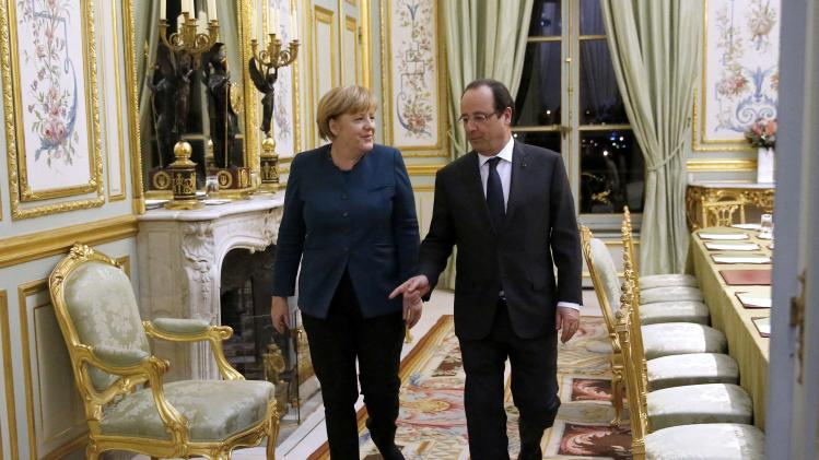 French President Hollande and German Chancellor Merkel walk at the Elysee Palace, in Paris