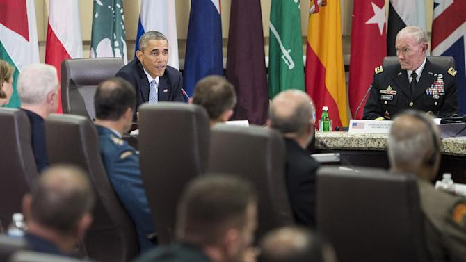 US Army Gen. Martin Dempsey(R), US Chairman of the Joint Chiefs of Staff, listens with others while US President Barack Obama makes a statement for the press after a meeting at Andrews Air Force Base October 14, 2014 in Maryland