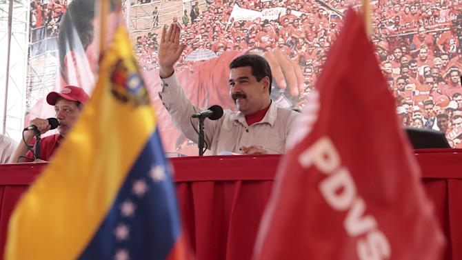 Venezuela's President Nicolas Maduro waves to supporters during a meeting with workers at a oil well operated by Venezuela's state oil company PDVSA in Morichal