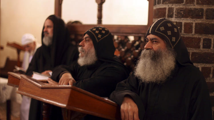 Clergymen pray during an early morning mass at the historic al-Muharraq Monastery, a centuries-old site some 180 miles (300 kilometers) south of Cairo in the province of Assiut. Egypt, Tuesday, Feb. 5, 2013. Egypt's Coptic Christian pope sharply criticized the country's Islamist leadership in an interview with The Associated Press on Tuesday, saying the new constitution is discriminatory and Christians should not be treated as a minority. (AP Photo/Khalil Hamra)
