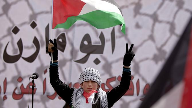 A Palestinian boy holds a national flag, during a rally in support of Palestinian President Mahmoud Abbas, ahead of his meeting with U.S. President Barack Obama, in the West Bank city of Ramallah, Monday, March 17, 2014. Abbas only faces bad options, from his perspective, as he heads into a White House meeting Monday with Obama. He could accept a U.S.-proposed framework for an Israeli-Palestinian partition deal, he could reject it or he could agree to extend negotiations. (AP Photo/Majdi Mohammed)