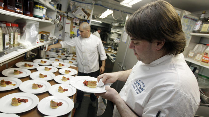 FILE - In this May 11, 2012 file photo, chef and owner Josiah Slone, right, prepares a foie gras dish at the Sent Sovi restaurant in Saratoga, Calif. California's ban on foie gras could be a boon for at least one San Francisco restaurant. The Presidio Social Club is on federal land, so it's exempt from the restriction. And it's flaunting the exemption, advertising its foie gras options. (AP Photo/Marcio Jose Sanchez, File)