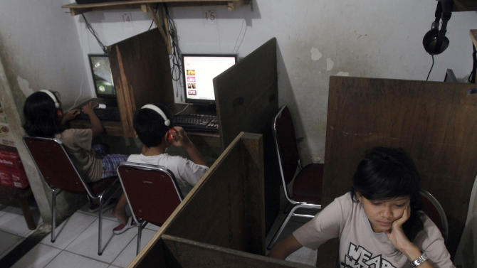 In this Friday, Oct. 19, 2012 photo, Indonesian youths browse at an internet cafe in Jakarta, Indonesia. There are growing numbers of incidents involving internet social media networks being used as a mean for children trafficking in Indonesia, at least eight reported this month alone of young girls being abducted and enslaved by men who approached them randomly on Facebook, raising concerns that the overall number of trafficked children remains grossly underestimated in the sprawling archipelago of 240 million. (AP Photo/Tatan Syuflana)