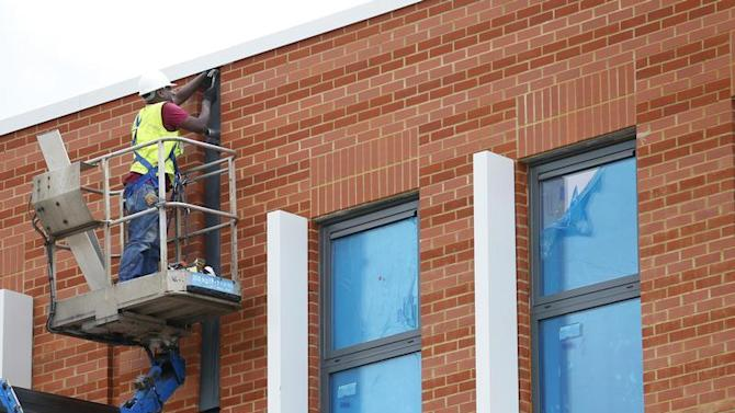 A construction worker stands on a 'cherry picker' at a housing development project in south London
