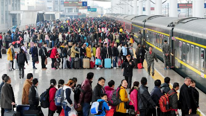 Passengers wait to board a train at a railway station during the Chinese Lunar New Year travel rush, in Jiujiang