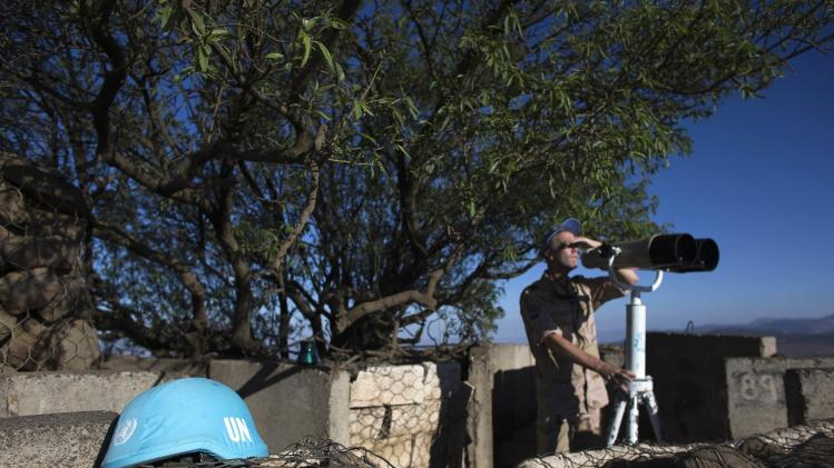 A member of the U.N. Disengagement Observer Force keeps watch of the Syrian side of Quneitra crossing