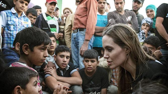 This June 18, 2013 photo released by the United Nations High Commissioner for Refugees (UNHCR) shows special envoy Angelina Jolie, right, speaking with Syrian refugees in a Jordanian military camp based near the Syria-Jordan border. The Syrian civil war contributed to pushing the numbers of refugees and those displaced by conflict within their own nation to an 18-year high of 45.2 million worldwide by the end of 2012, the U.N. refugee agency said Wednesday, June 19. Most of the refugees in the world have fled from five war-affected countries: Afghanistan, Somalia, Iraq, Syria and Sudan. (AP Photo/United Nations High Commissioner for Refugees , O. Laban-Matte)
