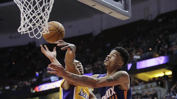 Phoenix Suns' Gerald Green, right, is fouled by Los Angeles Lakers' Wesley Johnson during overtime of a preseason NBA basketball game on Tuesday, Oct. 21, 2014, in Anaheim, Calif. The Suns won 114-108. (AP Photo/Jae C. Hong)