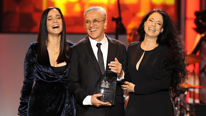 Caetano Veloso, center, accepts his award at the 2012 Latin Recording Academy Person of the Year Tribute to Caetano Veloso at the MGM Grand Garden Arena on Wednesday, Nov. 14, 2012, in Las Vegas. Presenting the award from left are Julieta Venegas and Sonia Braga. Photo by Powers Imagery/Invision/AP)