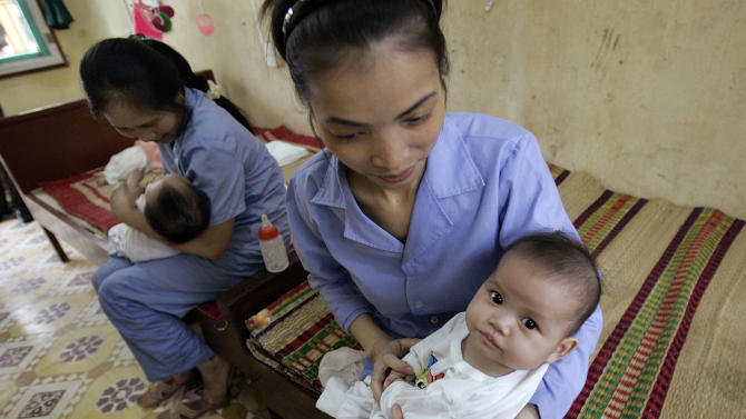 FILE - In this April 23, 2008 file photo, five-month-old baby girls are held by workers at an orphanage in Bac Ninh province, near Hanoi, Vietnam. Vietnam and the United States are close to an agreement allowing Americans to adopt Vietnamese children again, five years after a ban was imposed amid allegations of baby-selling and babies offered without parents' consent, a visiting U.S. Sen. Mary Landrieu, D-La, said Wednesday, Feb. 21, 2013. Vietnam was a popular destination for prospective adoptive parents before Washington imposed the ban in 2008 following a U.S. investigation. (AP Photo/Chitose Suzuki, File)