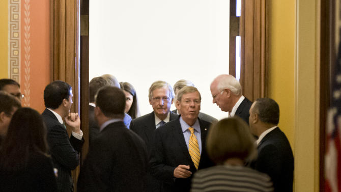 Senate Minority Leader Mitch McConnell, R-Ky., center, emerges from a closed-door meeting with Republican senators at the Capitol in Washington, Wednesday, Oct. 16, 2013. McConnell and his Democratic counterpart, Senate Majority Leader Harry Reid, D-Nev., reached last-minute agreement Wednesday to avert a threatened Treasury default and reopen the government after a partial, 16-day shutdown. Sen. Johnny Isakson, R-Ga., center right, speaks with Sen. Saxby Chambliss, R-Ga., right. (AP Photo/J. Scott Applewhite)