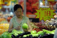 A shopper selects vegetables at a market in Hefei, China's Anhui province. Data in the current third quarter have remained weak as the slack global economy dents demand for exports and domestic activity weakens