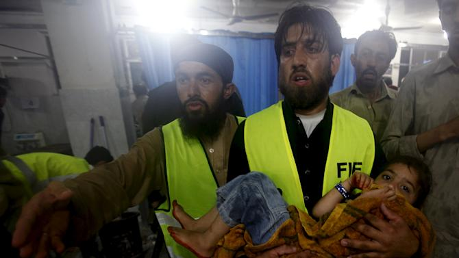 A child is taken to Leady Reading Hospital for treatment after torrential rains caused flooding and houses to collapse in Peshawar