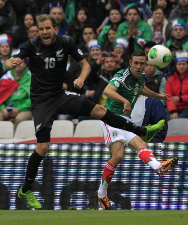 Miguel Layun of Mexico kicks the ball past Jeremy Brockie of New Zealand during their 2014 World Cup qualifying playoff first leg soccer match at the Azteca stadium in Mexico City