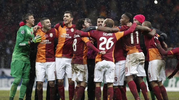 Galatasaray players celebrate their victory against Juventus at the end of their Champions League soccer match at Turk Telekom Arena in Istanbul
